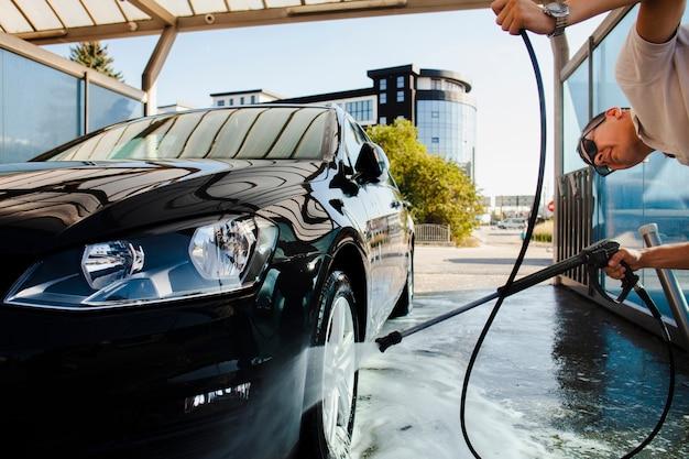 Mens die zorgvuldig een autowiel schoonmaakt