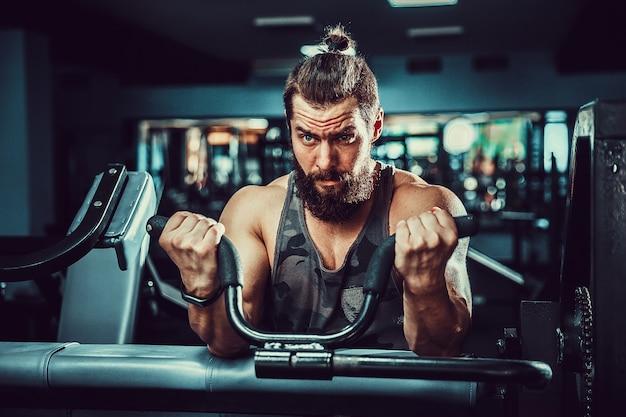 Mens die zwaargewicht oefening voor bicepsen op machine in een gymnastiek doet
