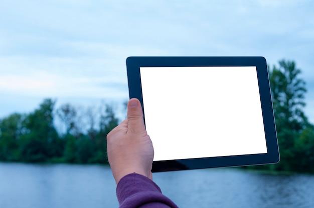 Mens die zwarte tablet in hand met het lege witte scherm houden bij de rivier
