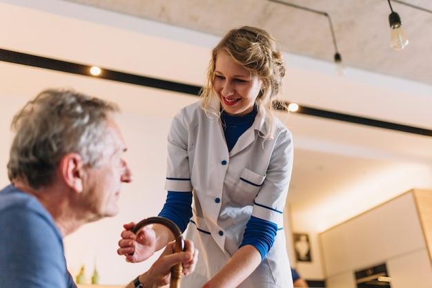 Mens en glimlachende verpleegster in pensioneringshuis