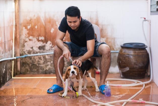 Mens en leuke puppybrak die een douche neemt