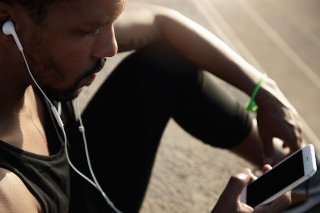 Mens en technologie concept. mensen en sport. knappe afrikaanse kerel die in hoofdtelefoons aan muziek luisteren die zijn slimme telefoon met het lege ruimtescherm van de exemplaar voor uw reclametekst of informatie gebruiken