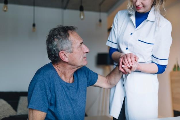 Mens en vriendschappelijke verpleegster in oude dag naar huis