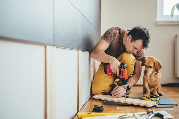 Mens en zijn hond die het renovatiewerk thuis doen