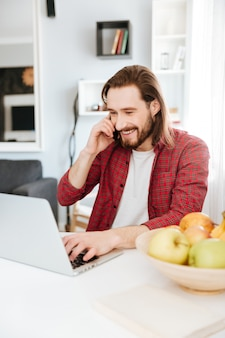 Mens gebruikend laptop en thuis sprekend op celtelefoon