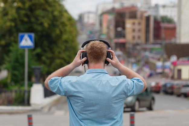Mens het lopen het luisteren concept van muziekoortelefoons