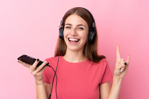 Mens het luisteren muziek over geïsoleerde roze muur