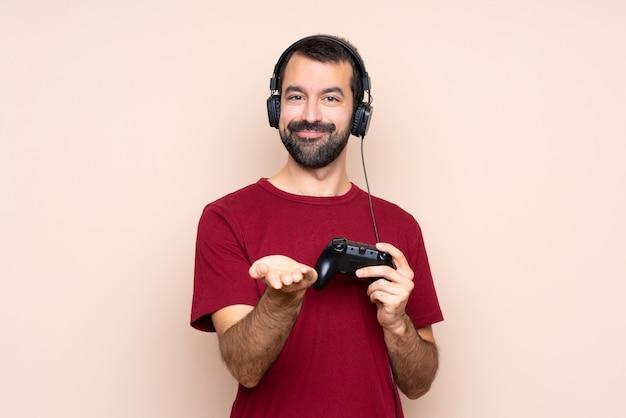 Mens het spelen met een videospelletjecontrolemechanisme over geïsoleerde muur die copyspace denkbeeldig op de palm houden om een advertentie op te nemen