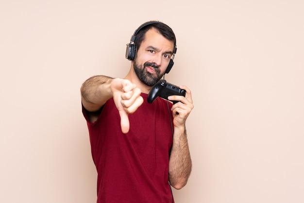 Mens het spelen met een videospelletjecontrolemechanisme over geïsoleerde muur die duim neer met negatieve uitdrukking tonen