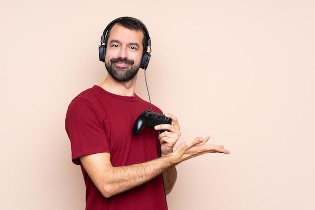 Mens het spelen met een videospelletjecontrolemechanisme over geïsoleerde muur die een idee voorstellen terwijl het kijken glimlachen naar