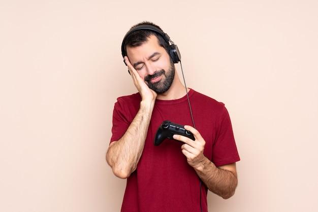 Mens het spelen met een videospelletjecontrolemechanisme over geïsoleerde muur die slaapgebaar in aanbiddelijke uitdrukking maken