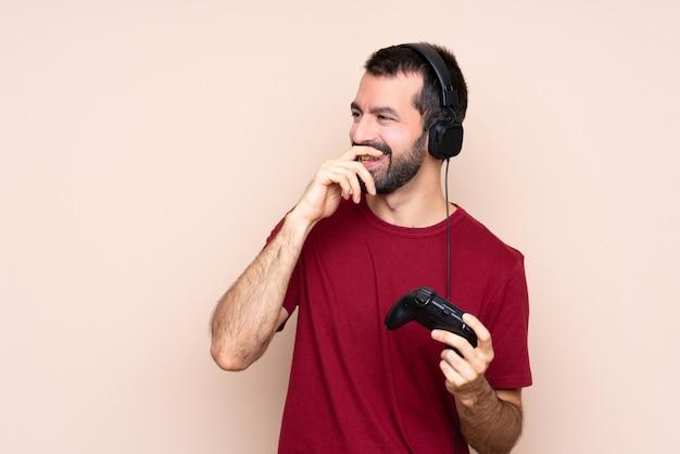 Mens het spelen met een videospelletjecontrolemechanisme over geïsoleerde muur die veel glimlacht