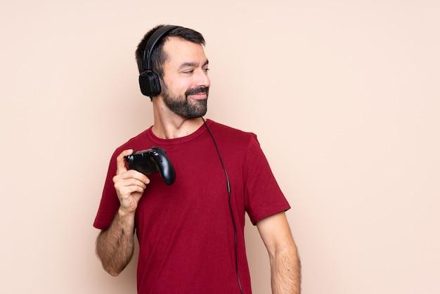 Mens het spelen met een videospelletjecontrolemechanisme over geïsoleerde muur met gekruiste en gelukkige wapens