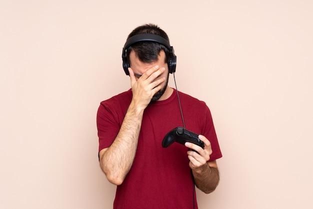 Mens het spelen met een videospelletjecontrolemechanisme over geïsoleerde muur met vermoeide en zieke uitdrukking