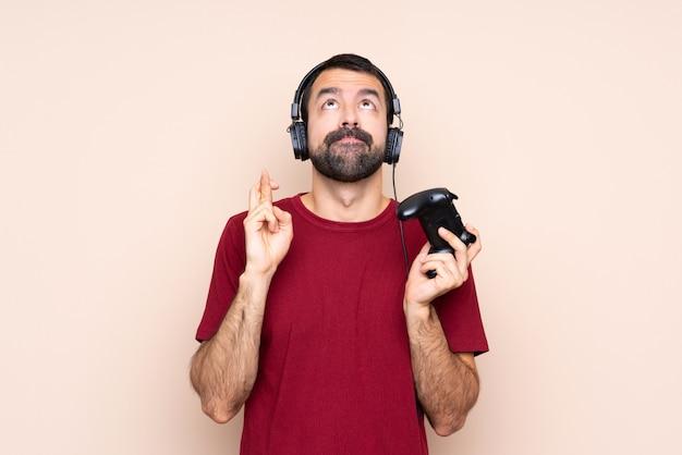 Mens het spelen met een videospelletjecontrolemechanisme over geïsoleerde muur met vingers die en het beste kruisen wensen