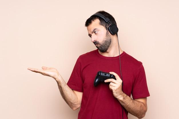 Mens het spelen met een videospelletjecontrolemechanisme over geïsoleerde muurholding copyspace met twijfels