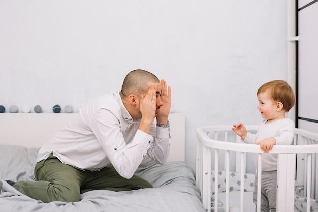 Mens het spelen met het glimlachen van weinig baby in voederbak in slaapkamer