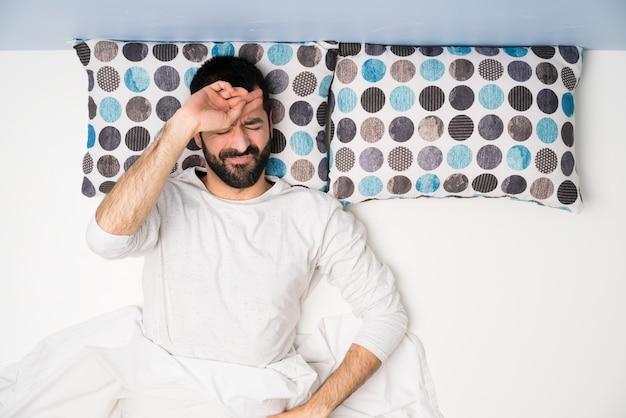 Mens in bed in hoogste mening met vermoeide en zieke uitdrukking