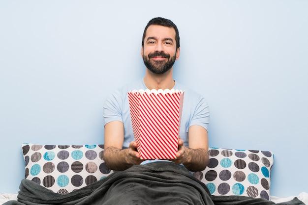Mens in bed met baard die popcorns eet