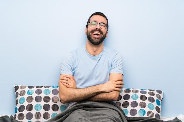 Mens in bed met glazen en het glimlachen