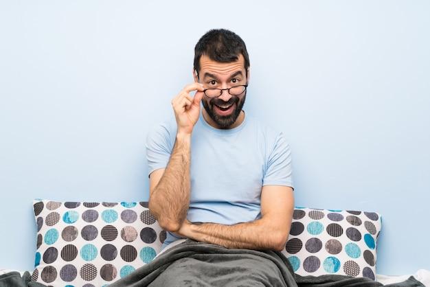 Mens in bed met glazen en verrast