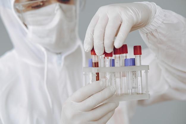 Mens in beschermend kostuum en glazen die bij laboratorium werken