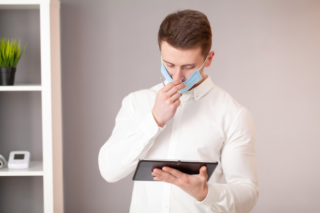 Mens in beschermend masker die bij tablet in bureau werken