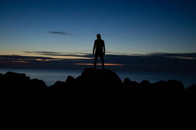 Mens in de kap die zich op de rotsen op overzeese achtergrond in avondtijd bevinden