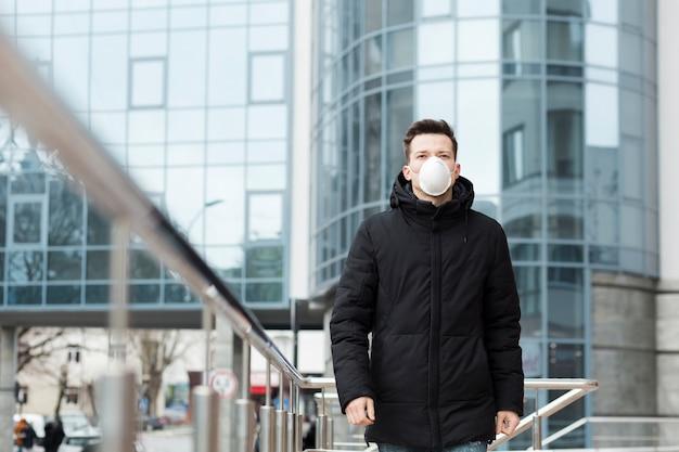 Mens in de stad die jas en medisch masker draagt