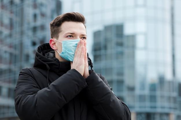 Mens in de stad die medisch masker en het bidden draagt