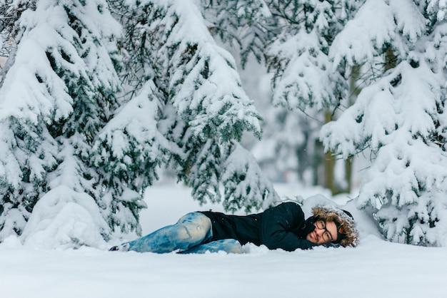 Mens in de winterkleren die in sneeuwbank onder de sneeuwbomen in koude de winterdag leunen.