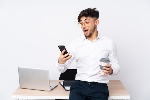 Mens in een bureau dat op de witte weg te halen koffie van de muurholding en mobiel wordt geïsoleerd