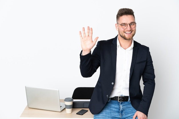 Mens in een bureau op witte muur wordt geïsoleerd die met hand met gelukkige uitdrukking groeten