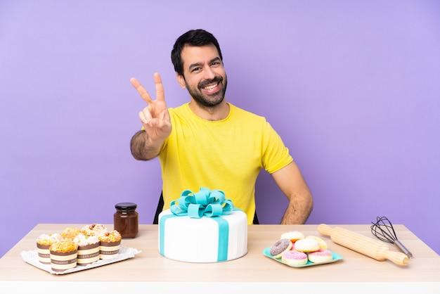 Mens in een lijst met een grote cake die en overwinningsteken glimlacht toont