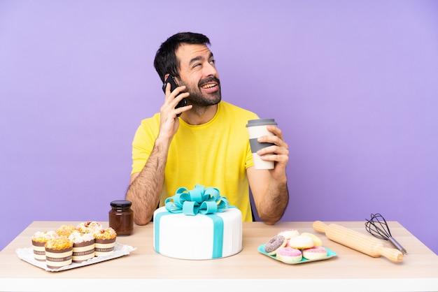 Mens in een lijst met grote cake over geïsoleerde purpere muur
