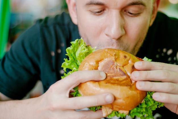 Mens in een restaurant dat een hamburger eet