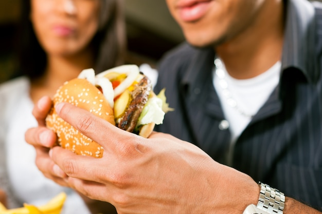 Mens in een restaurant dat hamburger eet