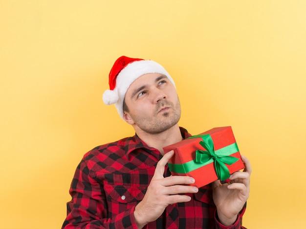 Mens in een rode hoed die een gift van kerstmis houdt