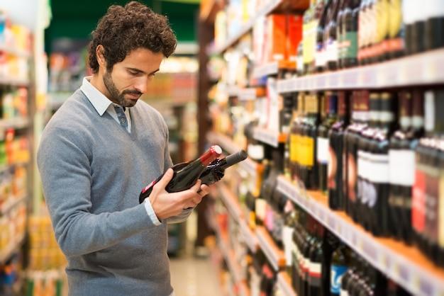 Mens in een supermarkt die een wijn kiest
