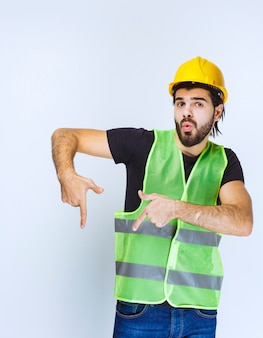 Mens in gele helm die hieronder iets toont.