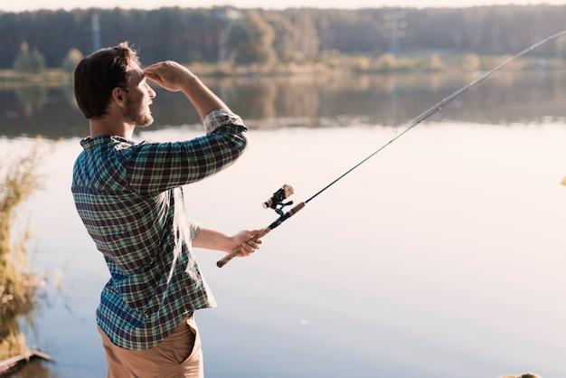 Mens in geruit overhemd die op rivier in de zomer vissen.