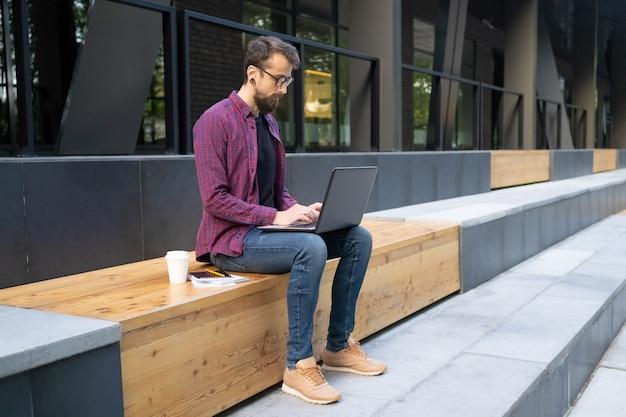 Mens in glazen die op houten bank zitten en op laptop typen