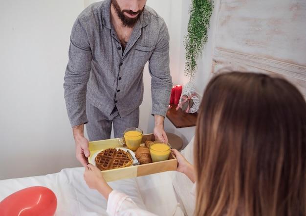 Mens in grijs gevend dienblad met romantisch ontbijt aan vrouw