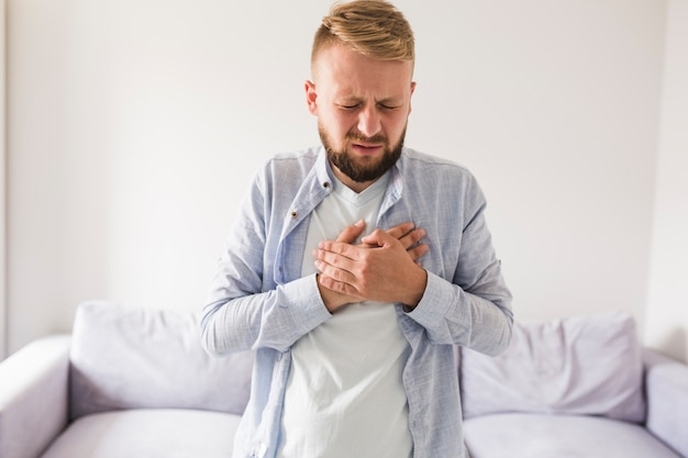 Mens in grijs overhemd die aan hartzeer lijden