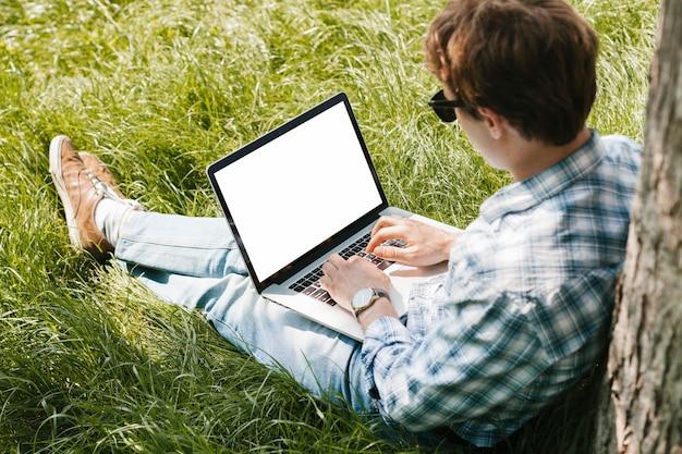 Mens in het park die aan laptop werken