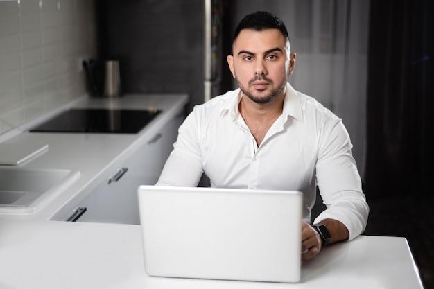 Mens in het witte overhemd websurfing met laptop in huiskeuken