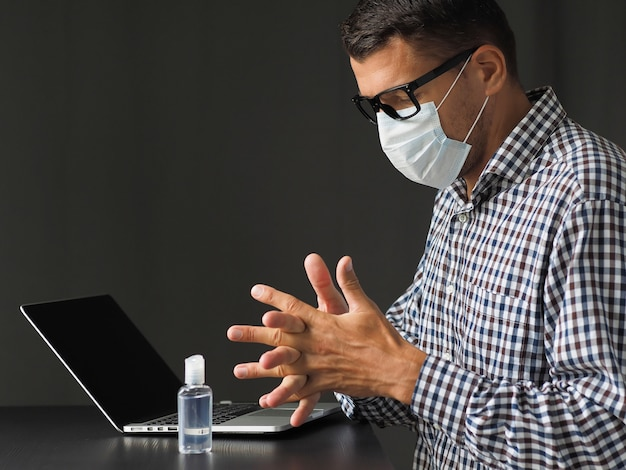 Mens in medisch masker die alcoholgel voor handdesinfecterend middel gebruiken na het werk met laptop toetsenbord. coronavirus in quarantaine plaatsen. thuiswerken. blijf veilig.