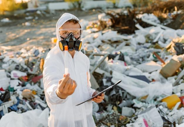 Mens in overall bij prullenbakpil. onderzoek doen. concept van ecologie, milieuvervuiling.