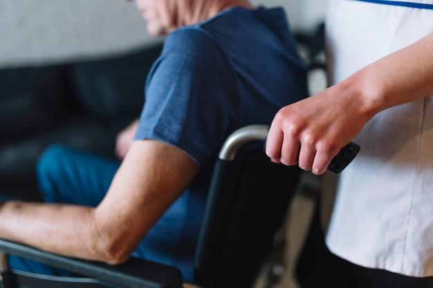 Mens in rolstoel in oude dag naar huis