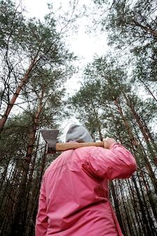 Mens in roze jasje in bos met bijl